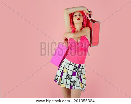 Girl wearing red wig and fashionable clothes. Woman with shopping bags. Sale and black friday. Fashion shopper posing on pink background. Holidays celebration concept copy space