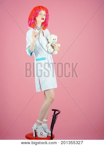 Nurse standing on chair on pink background. Girl examining teddy bear toy with syringe and stethoscope. Doctor and patient. Woman wearing medical uniform and red wig. Health care and cure concept.