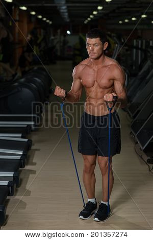Fitness man exercising with stretching band in the gym. Muscular sports man exercising with elastic rubber band. Guy working out with rubber band. fitness concept