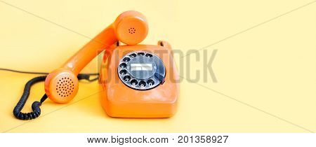 Vintage phone busy handset receiver on yellow background. Retro style orange telephone communication call center concept. Shallow depth field. copy space template.