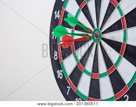 Red and green dart arrow hitting on center target of dartboard for aiming in business target.