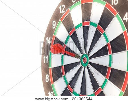 Red dart arrow hitting on center target of dartboard for success target concept.