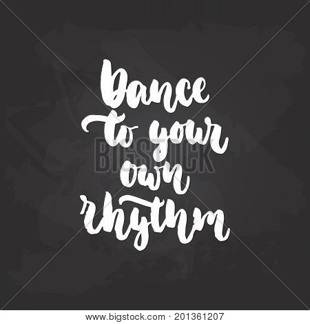 Dance to yor own rhythm - lettering dancing calligraphy quote drawn by ink in white color on the black chalkboard background. Fun hand drawn lettering inscription