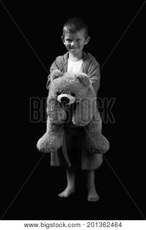 Naughty and funny boy with a teddy bear heading off to sleep in artistic conversion