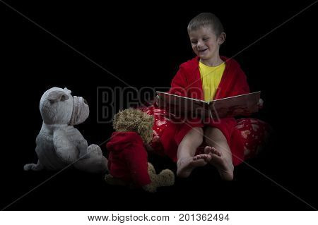 Funny boy with many stuffed animals reading a book before bed time artistic conversion