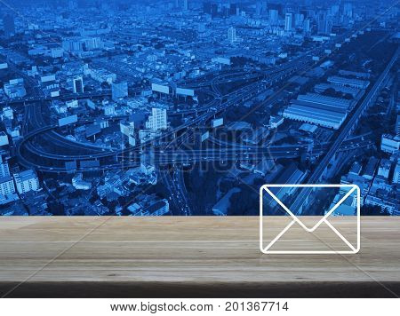 Mail icon on wooden table over aerial of modern city tower street and expressway Contact us concept
