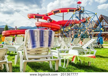 Empty loungers and big water slide in aquapark during summer