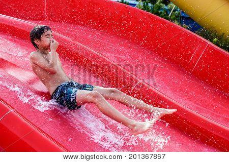 Happy boy sliding on a water slide in aquapark