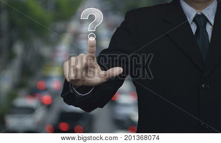 Businessman pressing question mark sign icon over blur of rush hour with cars and road Customer support concept
