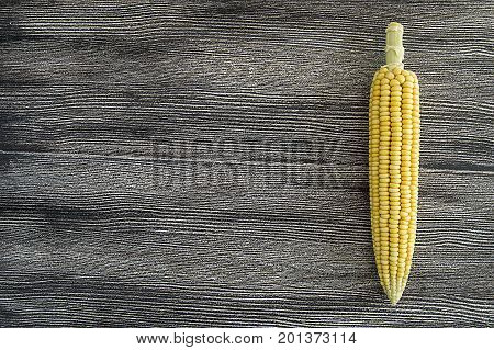 Grains of ripe corn. An ear of corn isolated. Corn on the cob, meal ripe juicy tasty corn. Photo of corn background.Fresh young sweet corn on cobs, closeup. Freshly picked ears of corn in bunch.Fresh organic corn, sweet corn on rustic wooden background