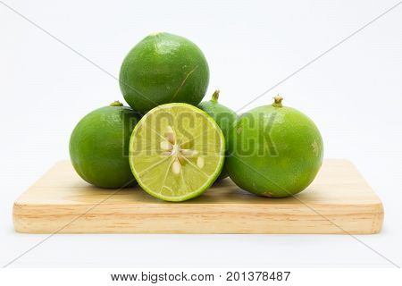 Slide fresh limes on wooden board on white background