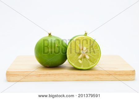 Fresh slide limes on wooden board on white background