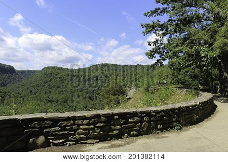 Overlook at Letchworth State Park in New York. Footpath with a stone wall. View of the forest and blue skies with white clouds