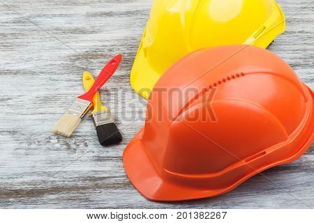 Two Construction Helmets And Paintbrushes