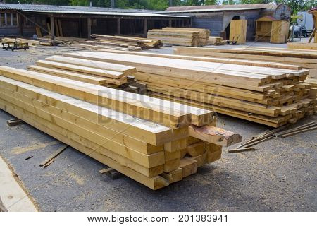 Sawmill. Warehouse for sawing boards on a sawmill outdoors. Wood timber stack of wooden blanks construction material