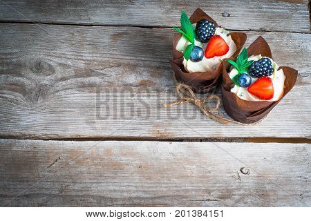 delicious sweet cupcakes decorated with cream chocolate cream cinnamon cocoa.decorated with fresh natural organic fruit cherry raspberry strawberry sugar mastic