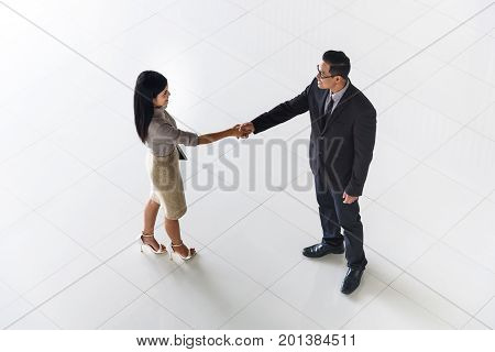 Top view Asian business people man and woman greeting by smiling and shaking hands