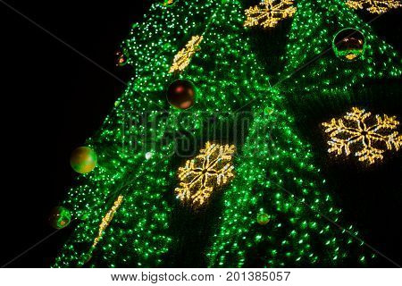 A Large Christmas Tree With Bright Garlands And Star Shine Lights Down On The Street In Winter. Deco