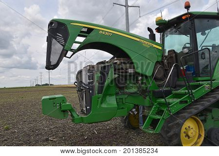 COMSTOCK, MINNESOTA, August 1, 2017: The John Deere 8430T tractor with an open hood is a product of John Deere Co, an American corporation that manufactures agricultural, construction, forestry machinery, diesel engines, and drive trains