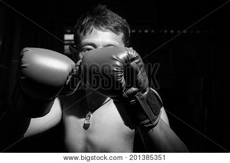 A man wore boxing gloves for boxing match. Selective focus on boxing gloves. Black and white image.