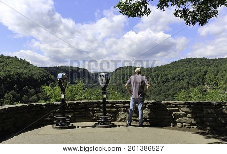Man viewing the forest and blue skies with white clouds. Coin operated binoculars in a stone walled overlook at Letchworth State park in New York.