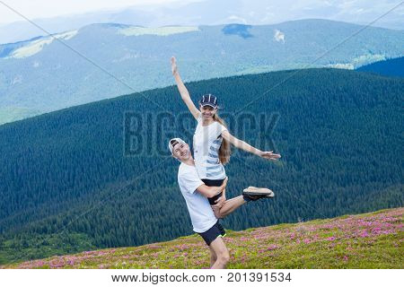 A happy young man holds a woman high in the mountains with a beautiful sky on background in a summer day. Hugging couple in love on a date high in the mountains. Very happy couple enjoy each other