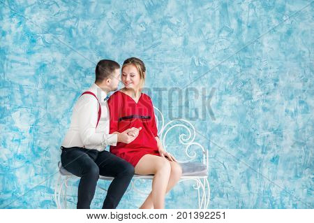 Loving young couple sitting on a bench, looking at each other and touching each other on a bench. Man and woman sitting on a bench. Studio shooting