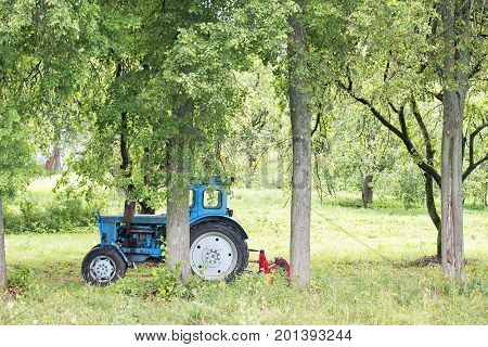 Old Russian rusty blue tractor in the garden