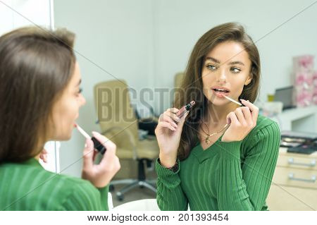 Young woman paints lips in beige in the dressing room before a mirror. Model paints lips in a professional studio makeup