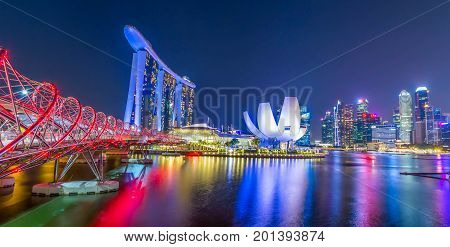 Singapore, Singapore - August 24, 2017: View at the Marina Bay in Singapore during the night with the iconic landmarks of The Helix Bridge.