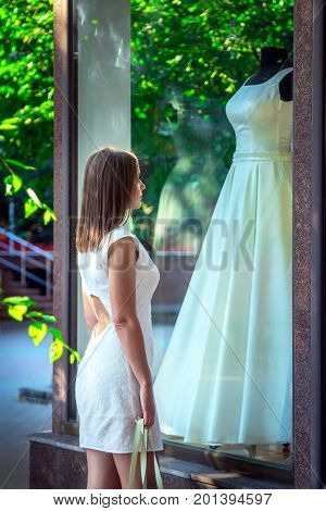 Elegant young woman admiring beautiful white wedding dress at show window of bridal boutique. Dreaming about wedding concept.