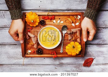 Hands holding wooden tray with autumn pumpkin soup decorated seeds and thyme in white bowl on rustic table top view. Cozy lifestyle shot for halloween menu.