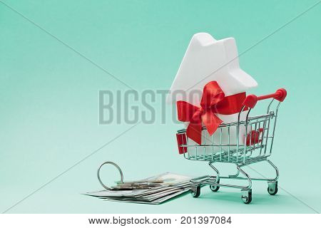 Small shopping cart with white house model decorated red bow ribbon dollars money and bunch of keys on green background. Buying a new home gift or sale of real estate concept.