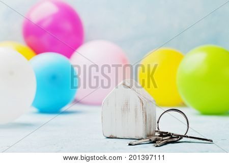Wooden house with bunch of keys and air balloons on light table. Housewarming moving real estate or buying a new home concept.