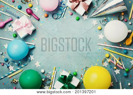 Holiday frame or background with colorful balloon gift confetti silver star carnival cap candy and streamer. Flat lay style. Birthday or party greeting card with copy space.