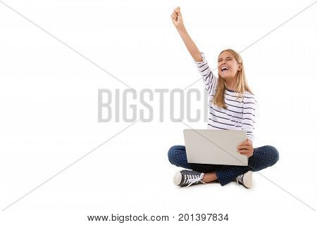 excited teen girl sitting on the floor celebrating success with one arm raisedisolated over white background with copyspace