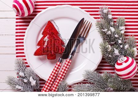 Holiday table setting. White plate knife and fork napkin and christmas decorations on white and red colors on white wooden table. Top view. Selective focus.