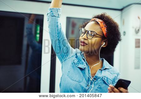 Young African Woman Listening To Music On The Subway