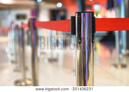 Stainless barricade with red rope on a blurred interior background.