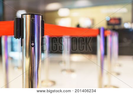 Stainless barricade with red rope on blurred interior background.