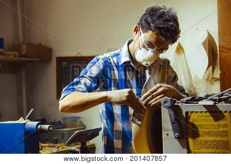 man turning a wooden plate on a lathe poster