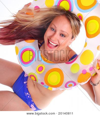 Happy young woman in swimsuit with life ring on the beach.