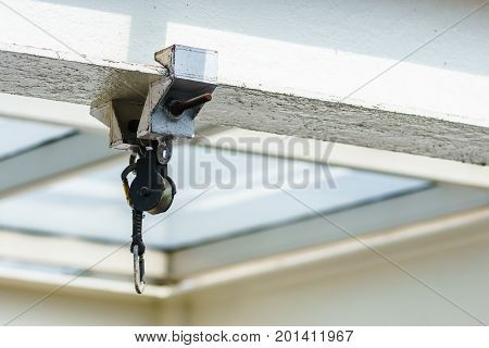 The pulley is mounted on the beam with glass roof background.