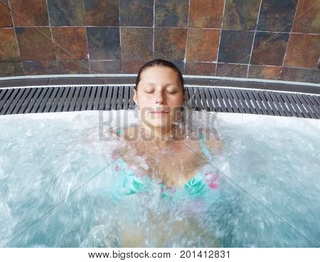 a relaxed woman doing hydromassage in a beauty spa