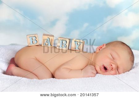 Four wooden blocks on a naked sleeping baby