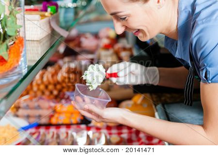 Working in a butcher's shop - a shop assistant with curd cheese