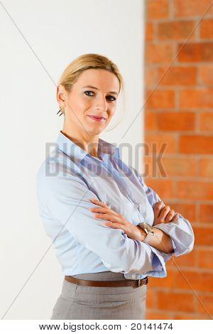 Realtor standing with folded arms in an empty apartment