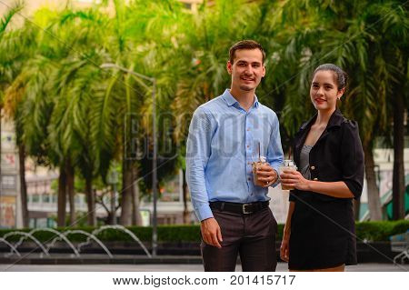 portrait of businessman and businesswoman stand and talk about business with Plastic Mug on hand outdor