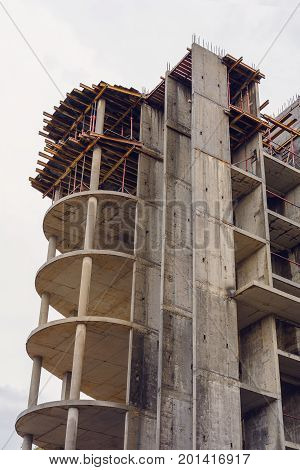 Construction of a monolithic concrete building on the background of a gray sky