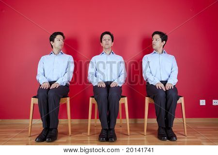 three nerd businessman with a suspicion look to each other, next to a red wall